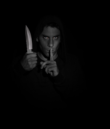 Evil man gesturing silence while holding a knife. Black and white, eyes in color photo