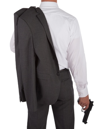 grabbing back: Man in a suit holding a gun viewed from behind isolated on white