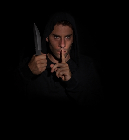 Evil man gesturing silence while holding a knife. photo