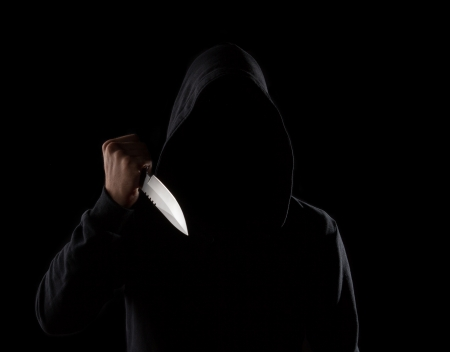 A dangerous hooded man standing in the dark and holding a shiny knife. Face can not be seen Archivio Fotografico