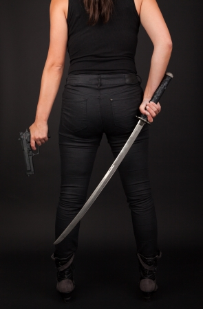 viewed from behind: Woman holding a gun and sword viewed from behind Stock Photo