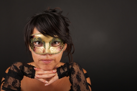 Attractive woman with a venetian mask leaning on her hands photo