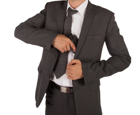 A man in a suit grabbing a gun out his jacket isolated on white photo