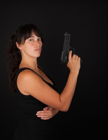 Woman holdin a gun against a dark background photo