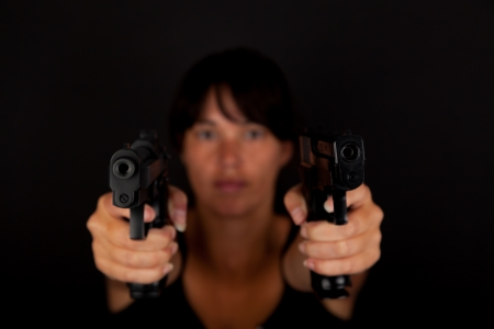 Woman aiming two guns against a dark background photo