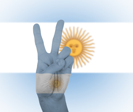 Hand peace sign, wrapped in the flag of Argentina photo