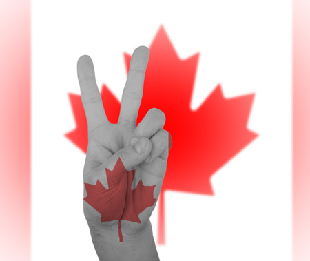 Hand peace sign, wrapped in the flag of Canada photo