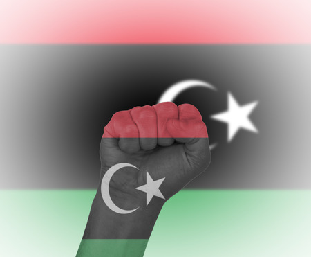 Fist wrapped in the flag of Libya and flag in the background photo