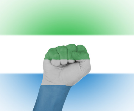 Fist wrapped in the flag of Sierra Leone and flag in the background photo