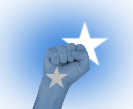 somalian flag: Fist wrapped in the flag of Somalia  and flag in the background Stock Photo