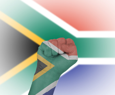 Fist wrapped in the flag of South Africa and flag in the background