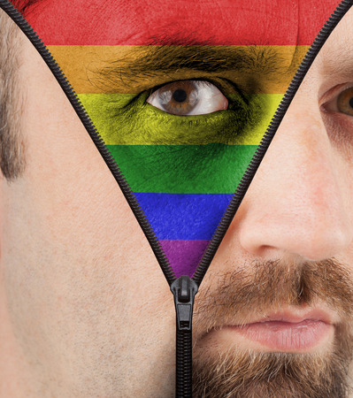 close-up of a face unzipping to show the rainbow flag for gay pride support