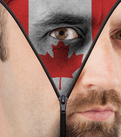 close-up of a face unzipping to show the flag of Canada photo