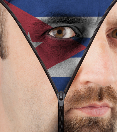 close-up of a face unzipping to show the flag of Cuba photo
