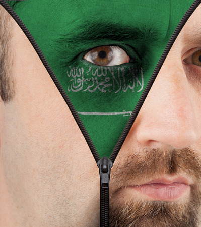 close-up of a face unzipping to show the flag of Saudi Arabia photo