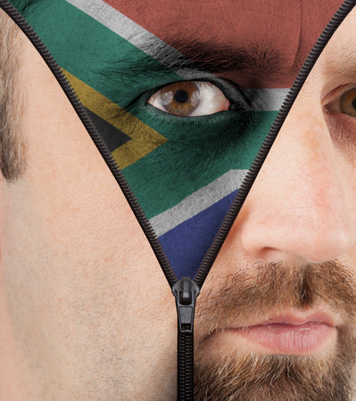 close-up of a face unzipping to show the flag of South Africa photo