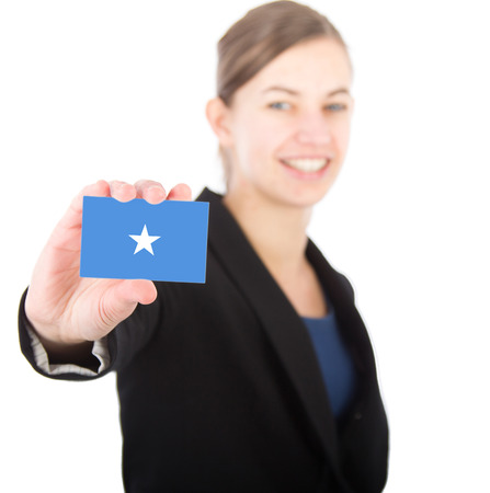 somalian flag: business woman holding a card with the flag of Somalia. With focus on the card