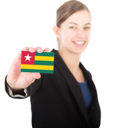 business woman holding a card with the flag of togo. With focus on the card photo