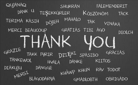 written text: Thank you word cloud written in many different languages on a chalkboard Stock Photo