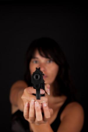 Woman aiming a gun against a dark background. With focus on the gun Stock Photo