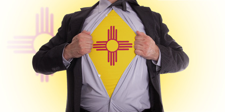 Businessman rips open his shirt to show his New Mexico flag t-shirt photo