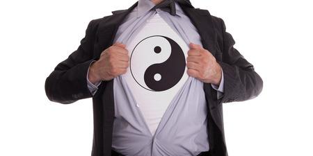 Businessman rips open his shirt to show his yin and yang t-shirt