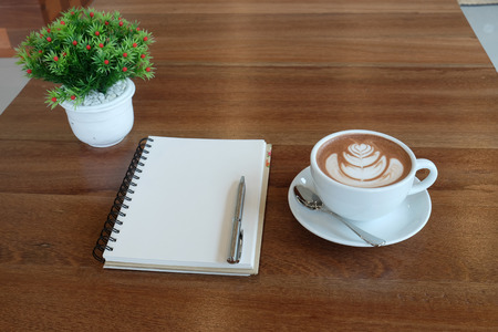 capuchino: The art of cocoa hot chocolate milk capuchino or esspresso.Selective focus a white cup of beautiful hot cocoa  blank white page of notebook and flowerpot  on wooden table. Stock Photo