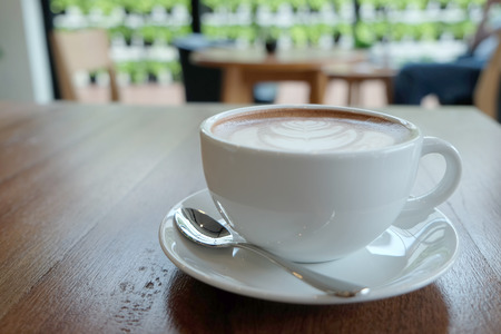 capuchino: A white cup of beautiful hot cocoa on wooden table and blur backgournd. The art of cocoa hot chocolate milk capuchino or esspresso.