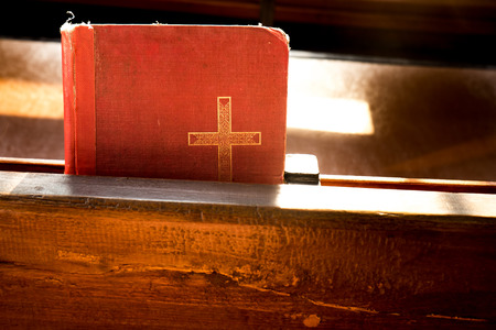 The old red books or red worship songbooks at wooden  bench in church  with soft sun light. Stock Photo