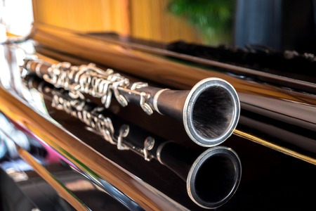 Black clarinet lying on closing grand piano.Colurful reflection.