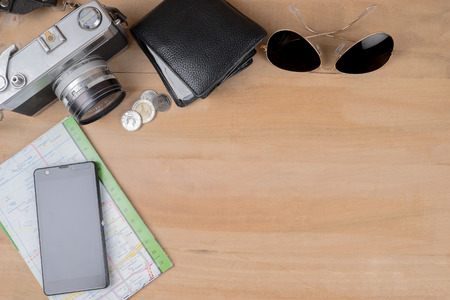 Prepare for travel concept. Vintage camera coins wallet sun glasses map and mobile on wooden table background