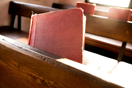 sun worship: The old red books or red worship songbooks at wooden  bench in church  with soft sun light. Stock Photo