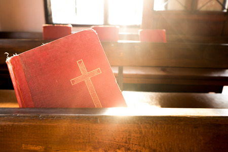 songbook: The old red books or red worship songbooks at wooden  bench in church  with soft sun light. Vintage Style. Stock Photo
