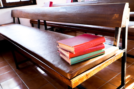 songbook: Red books stack on wooden bench. The red books are the old songbook in church.