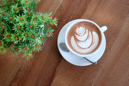 capuchino: A white cup of beautiful hot cocoa or hot chocolate milk on wooden table. The art of cocoa, hot chocolate milk ,capuchino or esspresso.