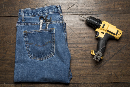 electric drill: Yellow Electric drill and Several tools on a denim workers pocket are on wooden background.