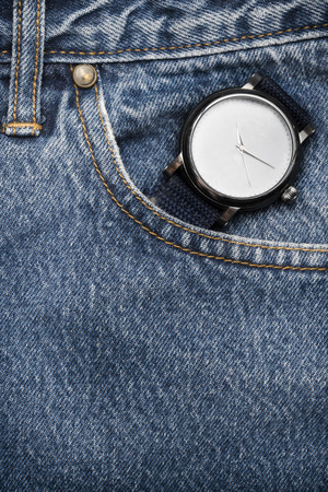 The old vintage wristwatch on a denim workers pocket photo