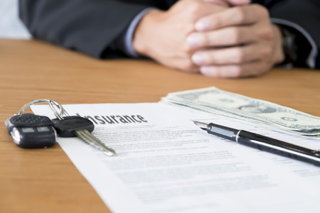pay for: closeup of a pen with car key, money to pay for car insurance. Stock Photo