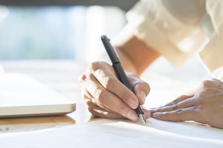 La donna di affari asiatica che firma un documento contratto di fare un affare.