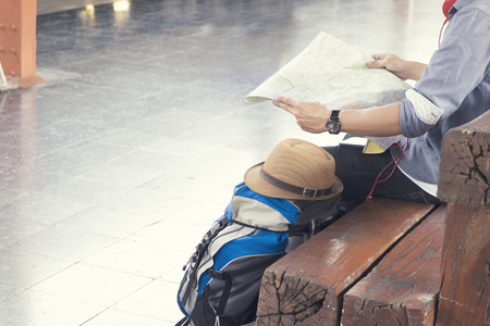 Traveler wearing backpack holding map, waiting for a train at trainstation and planing for next trip.Vintage tone, Retro filter effect, Soft focus, Low light.(selective focus) Stock Photo