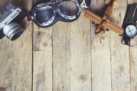 balsa: Vintage retro travel background. Retro camera, glasses, balsa wood model airplane and compass on wooden table background.