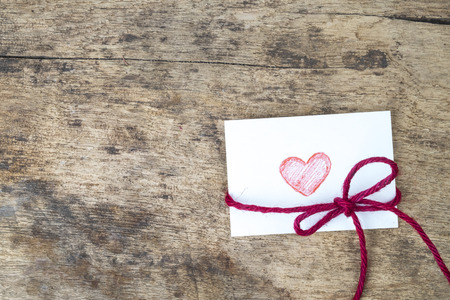 love letter: Valentine card with hand drawn red heart and red rope