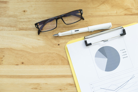 Top view of  analyze chart, glasses and pen on office wooden desktop.