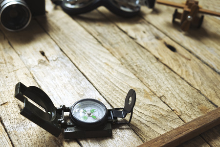 balsa: Compass on wooden background. Blur vintage camera, glasses and balsa wood model airplane. Vintage filter, travel concept. Stock Photo