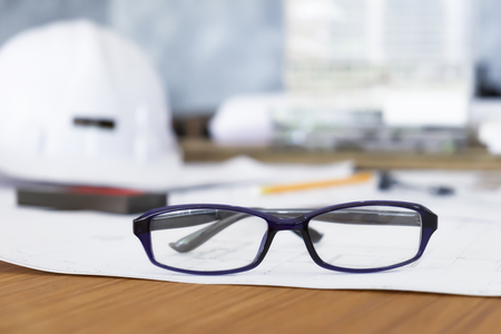 autocad: Glasses on engineer or architect working table in office. Construction and engineering concept background.
