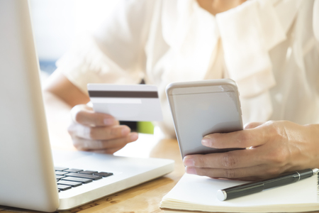 cvv: Woman holding mobile phone and credit card on laptop for online shopping