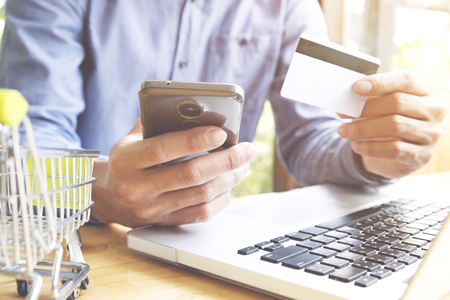 cvv: Man using laptop and mobile phone to online shopping and pay by credit card. Vintage tone, Retro filter effect, Soft focus, Low light.(selective focus)