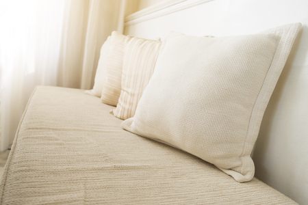 earth tone: Pillows on couch in the living room decorated with earth tone color. Relaxation, decoration or interior concept. Soft sunlight though the while curtain into the room. Stock Photo