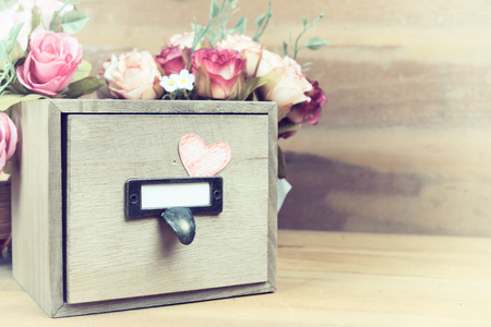 finding love: Vintage effect color of wood box with litter hand drawn red heart in fornt of rose flowers and wooden background. Love box, Hidden love, Finding love.
