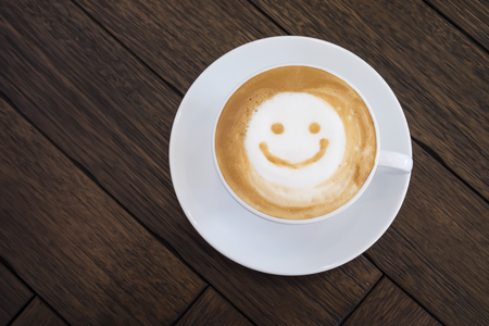 Top view white cup of latte art happy smile face on brown wooden table background wite copyspace.
